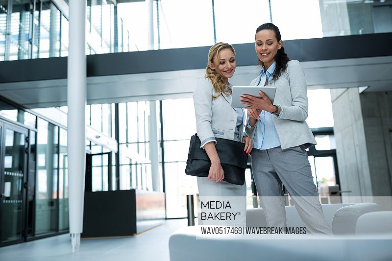 Businesswoman showing digital tablet to colleague