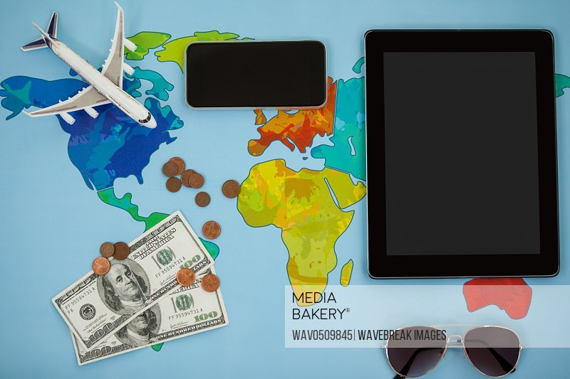 Electronic gadgets, sunglasses, dollar and airplane model on map