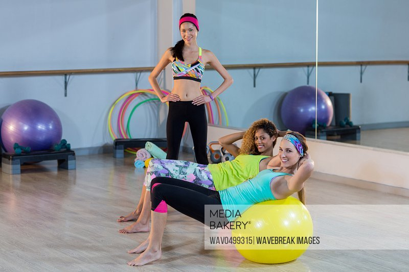 Women exercising on exercise ball with female trainer in gym