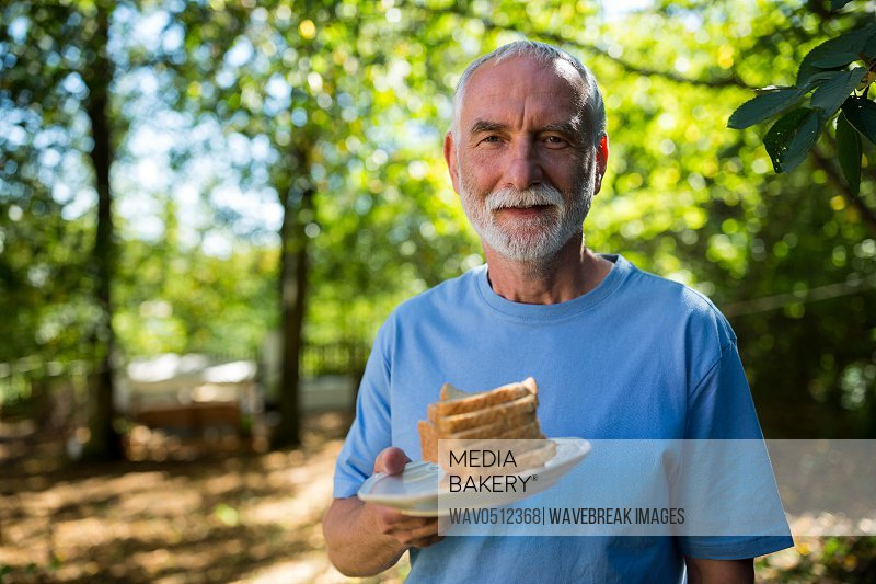 Portrait of senior man holding slice bread in a plate in garden on a sunny day