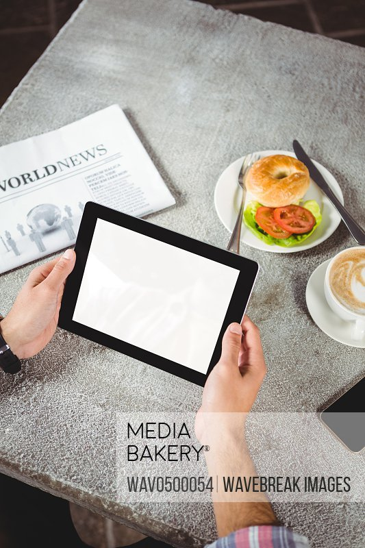 Hands of man holding digital tablet in cafeteria