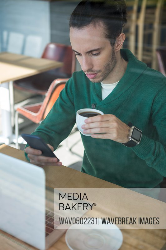 Man using mobile phone while having cup of coffee in cafeteria