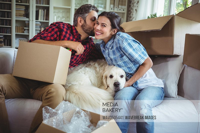 Man kissing woman while unpacking carton boxes in new house