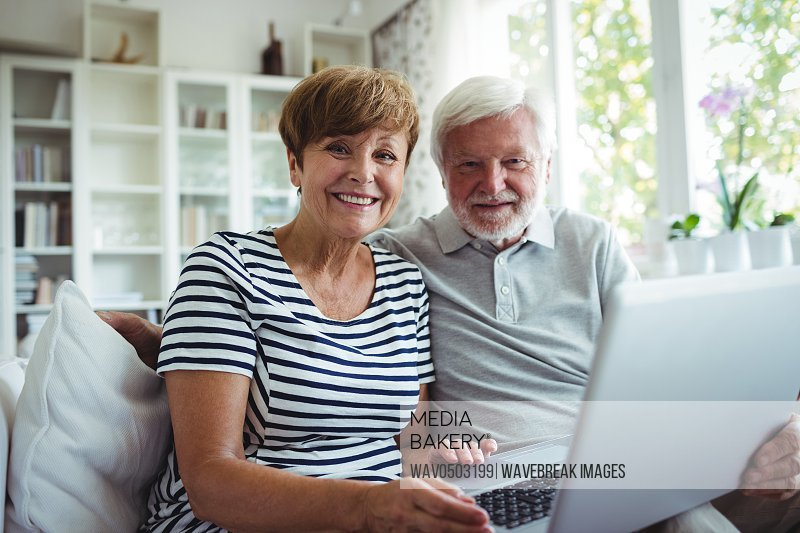 Portrait of senior couple sitting on sofa with a laptop in living room