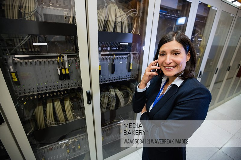 Beautiful technician talking on mobile phone in server room