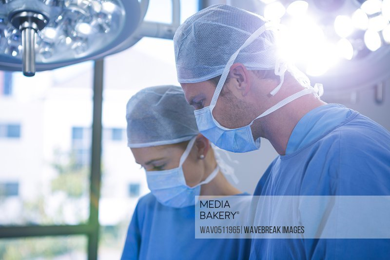 Female and male surgeon wearing surgical mask in operation theater at hospital