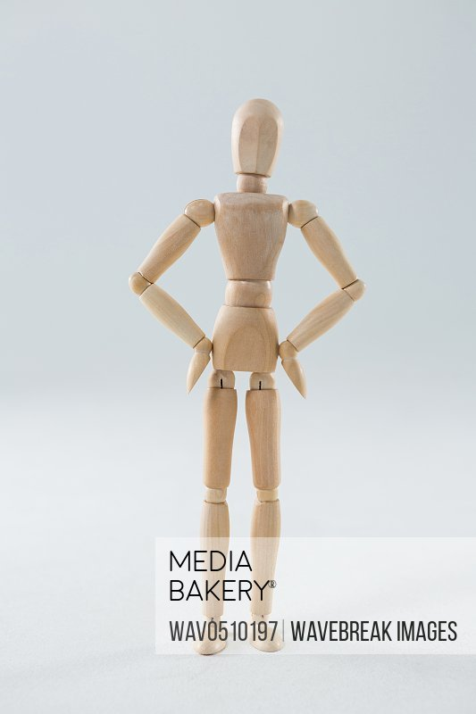 Wooden figurine standing with hands on hip on wooden background
