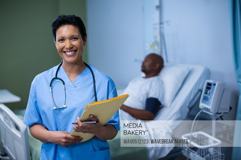 Portrait of female nurse standing with file in ward of hospital