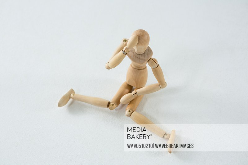 Tired wooden figurine with hand on forehead against white background