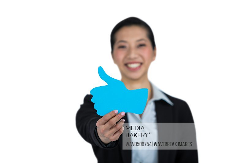 Portrait of businesswoman showing thumbs up sign board against white background