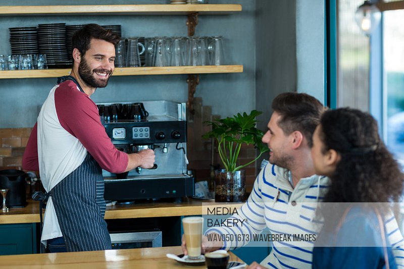 Smiling customer interacting with waiter in cafA?