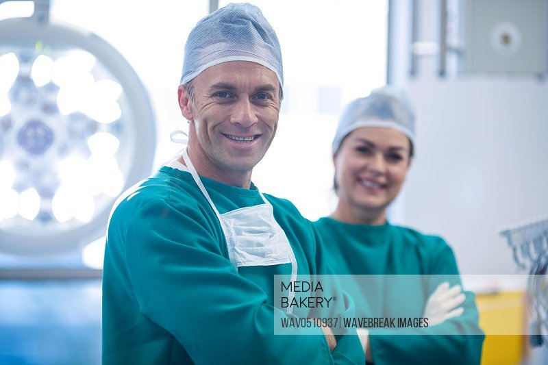 Portrait of surgeons standing with arms crossed in operation room at the hospital