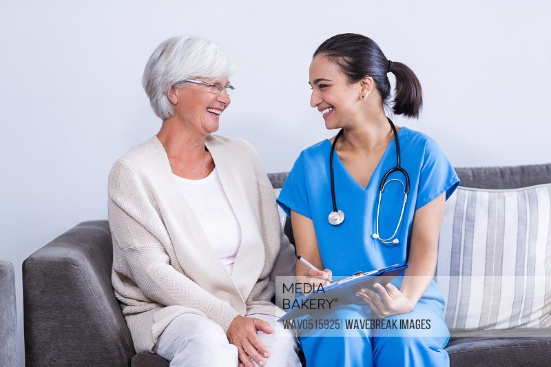 Doctor and senior woman discussing on clipboard