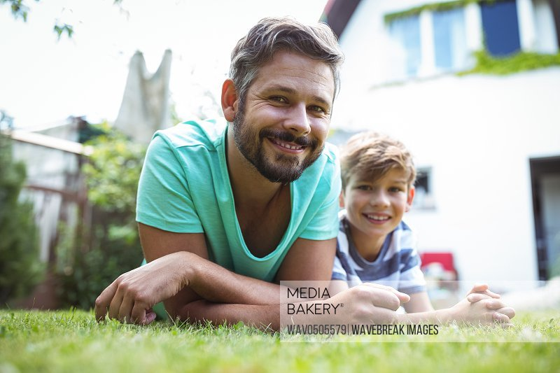 Father and son lying on grass in garden