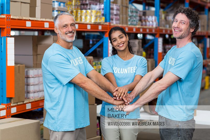 Portrait of happy volunteers putting hands together in a warehouse