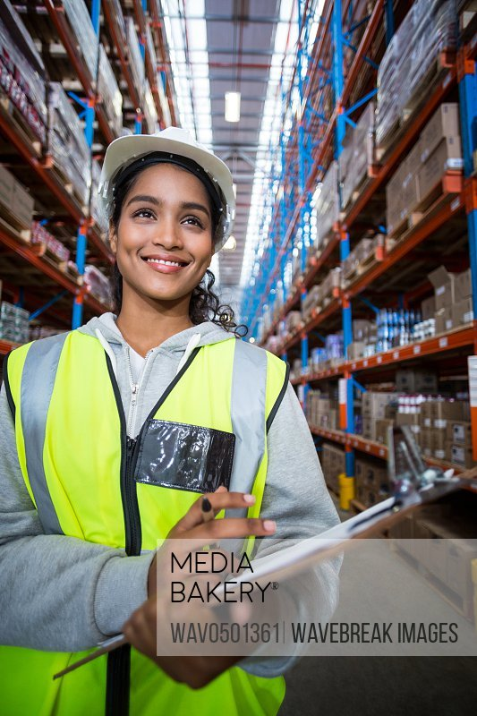 Female warehouse worker holding on clipboard in warehouse
