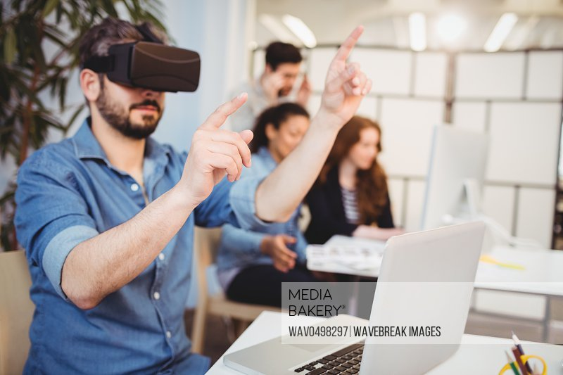 Businessman gesturing while using virtual reality headset against coworkers