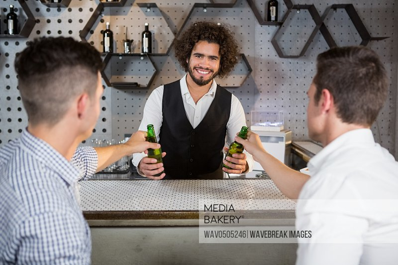 Bartender serving glass of beer to customers at bar counter in bar