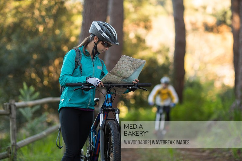 Female biker looking at a map with mountain bike in countryside
