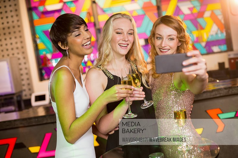 Three smiling female friends taking selfie from mobile phone while having champagne in bar