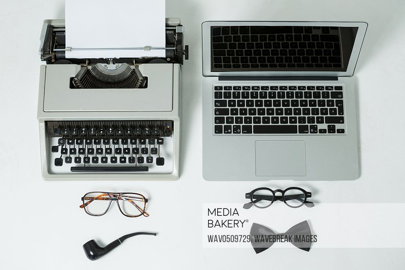 Vintage typewriter and modern laptop with spectacles, smoking pipe and bow on white background