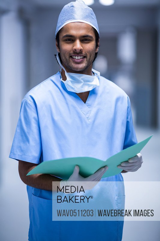 Portrait of surgeon holding a report in corridor at hospital