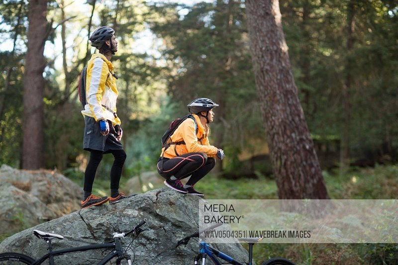 Biker couple looking at a view in countryside forest