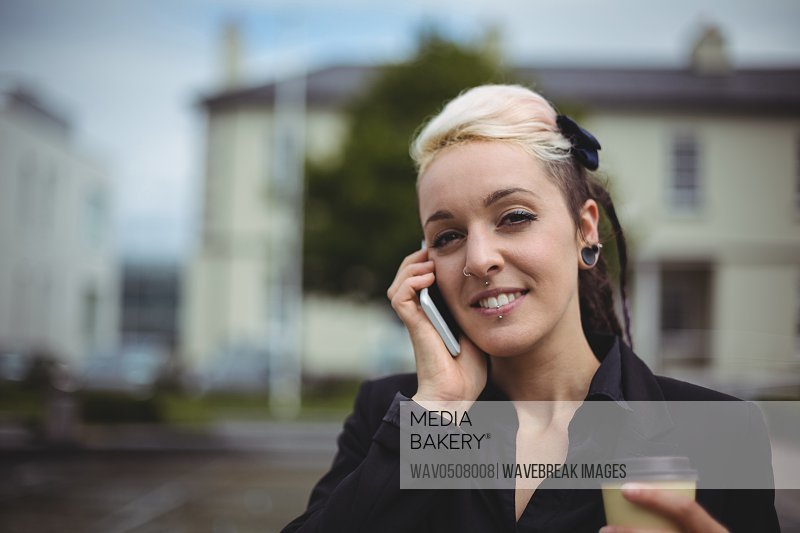 Portrait of businesswoman talking on mobile phone while holding disposable coffee cup in office campus