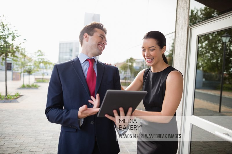 Businessman and colleague discussing over digital tablet and laughing