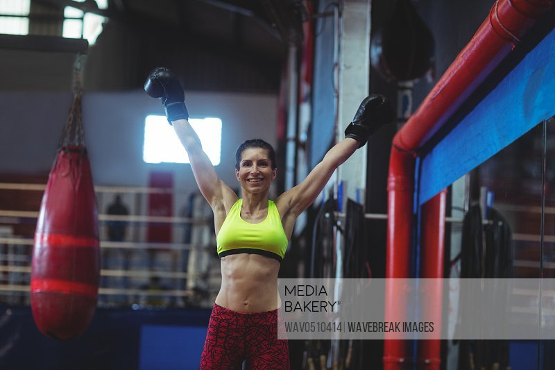 Portrait of excited female boxer posing after victory in fitness