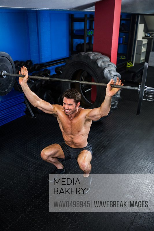 High angle view of shirtless man lifting barbell in gym