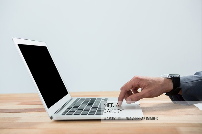 Hand of businessman using laptop in office
