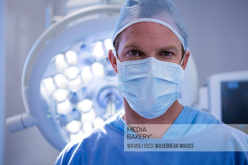 Portrait of male surgeon wearing surgical mask in operation theater at hospital