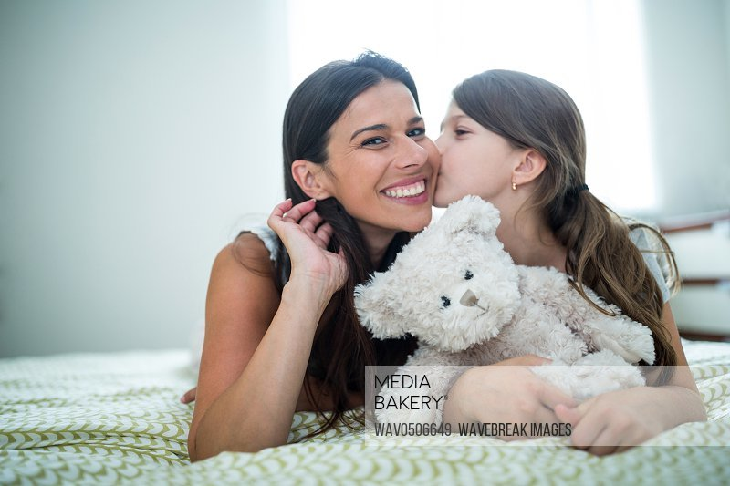 Daughter kissing on mother cheeks on bed at home