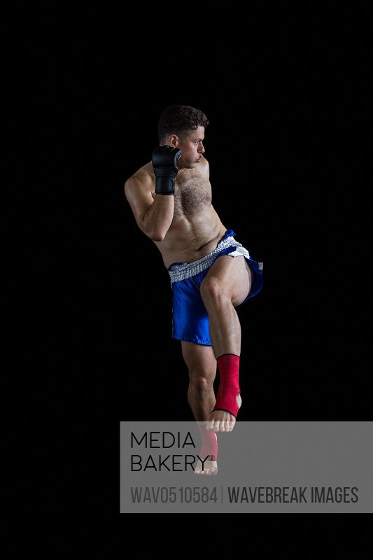 Boxer performing boxing stance against black background
