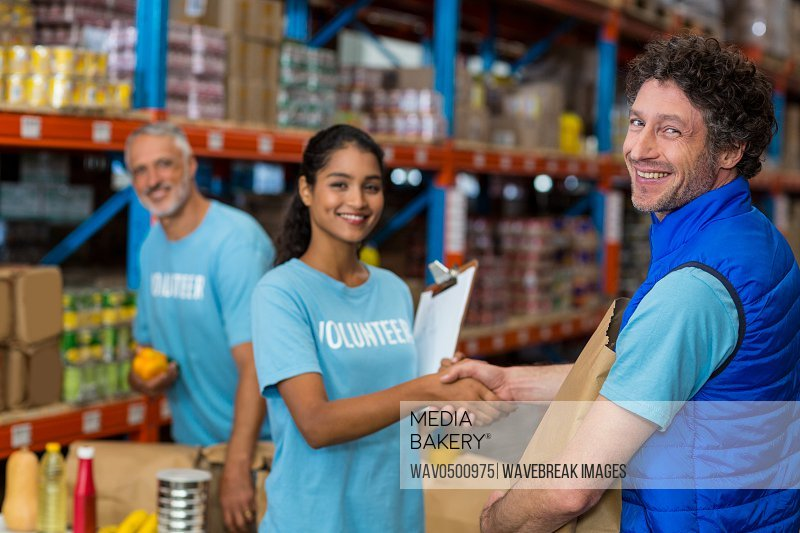 Portrait of volunteers shaking hands while working in warehouse