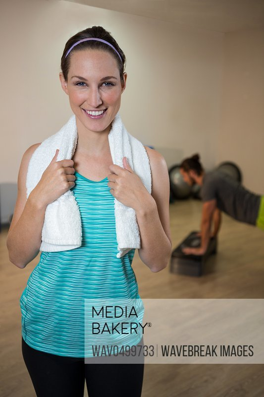 Portrait of smiling woman standing in fitness studio with napkin
