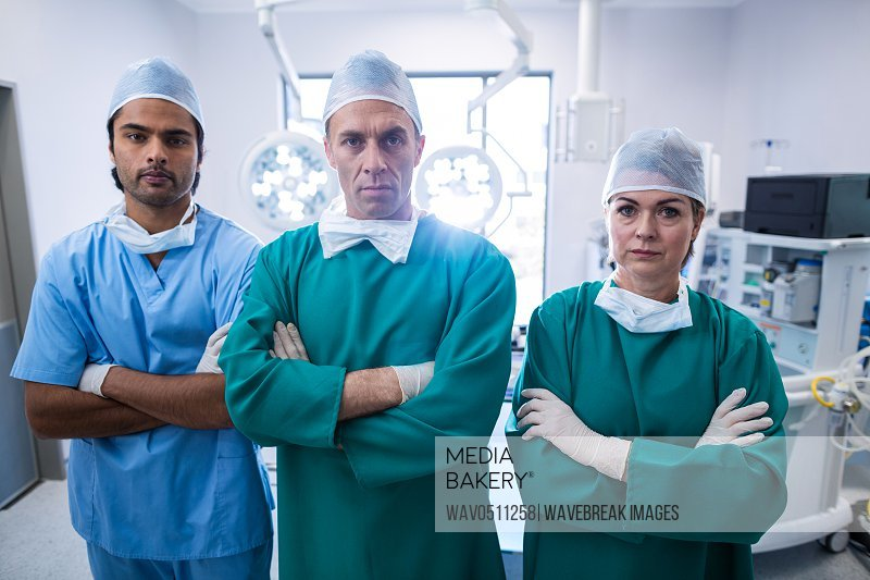 Portrait of surgeons standing with arms crossed in operation room at hospital