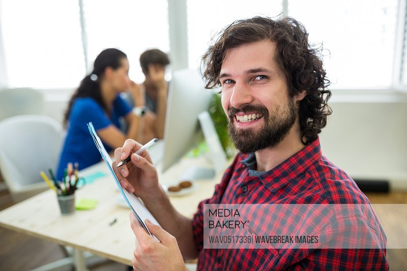 Portrait of smiling business executives writing on paper