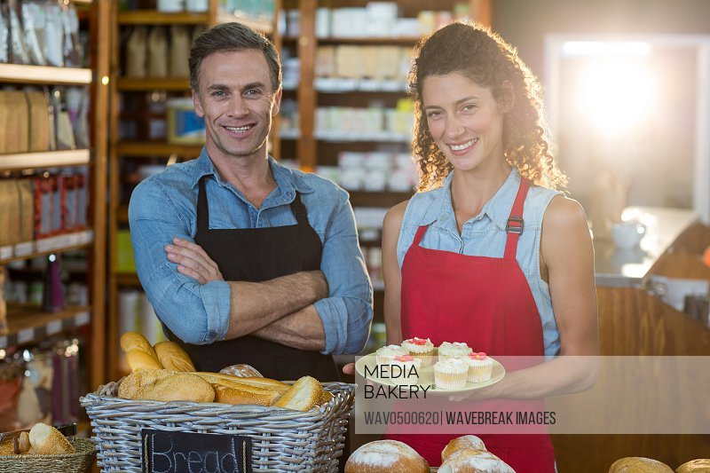 Portrait of smiling staff standing at bakery counter in supermarket