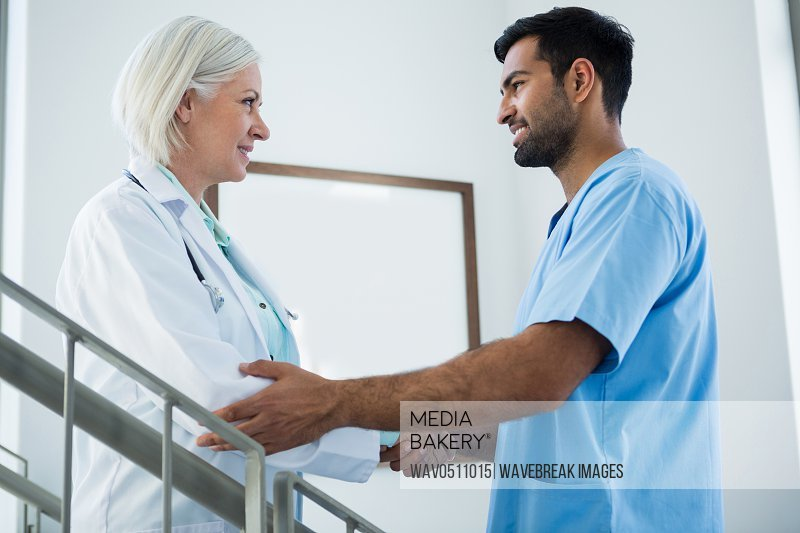 Doctors standing on staircase and shaking hands in hospital