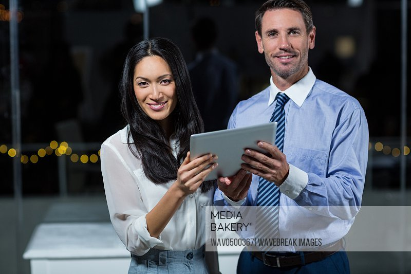 Portrait of businessman and colleague holding digital tablet in the office
