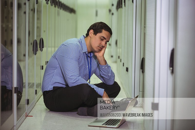 Stressed technician sitting on floor and looking at laptop in server room