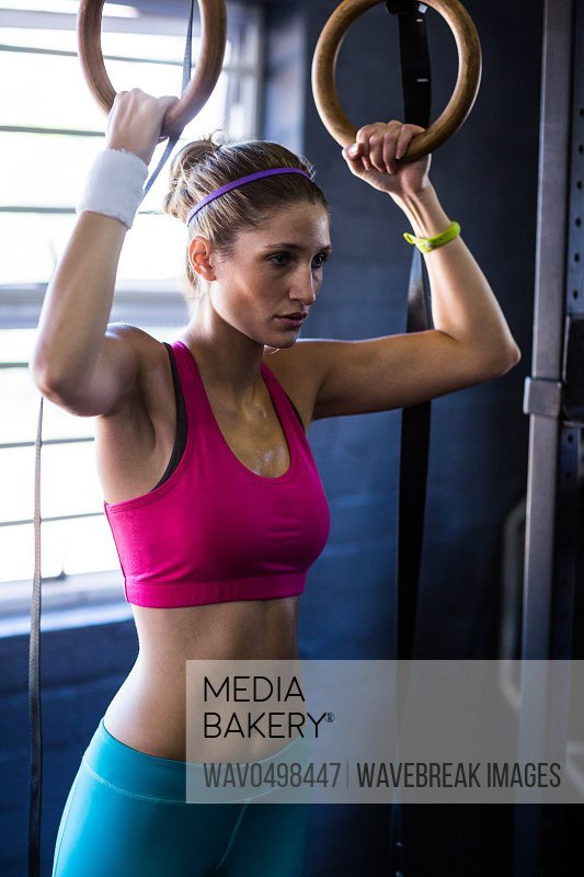 Serious woman holding gymnastic rings while exercising in gym