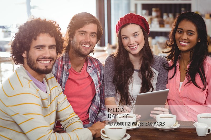 Group of friends using digital tablet while having cup of coffee in cafe