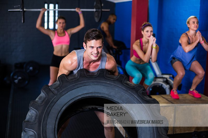 Smiling man lifting tire while exercising in gym
