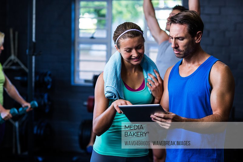 Male and female athletes looking in tablet computer while standing at gym