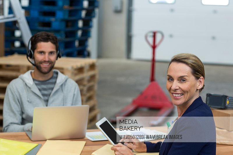 Portrait of warehouse managers using digital tablet laptop in warehouse