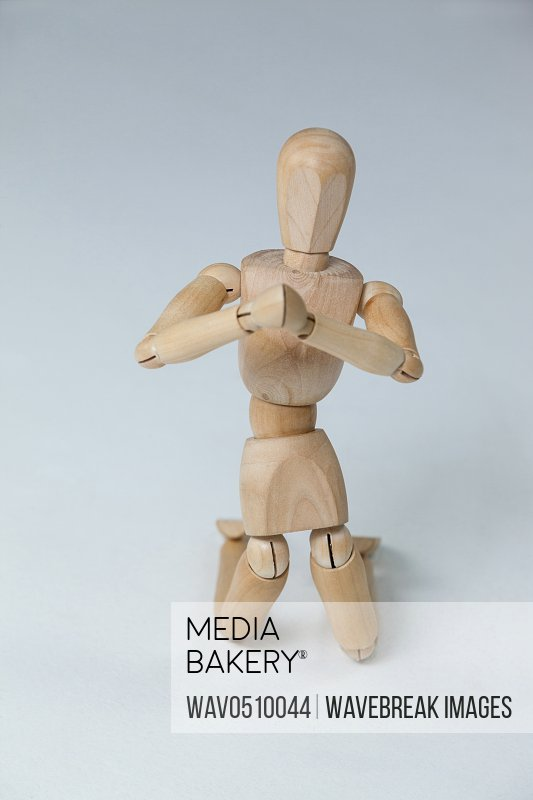 Wooden figurine kneeling with both hands joined against white background