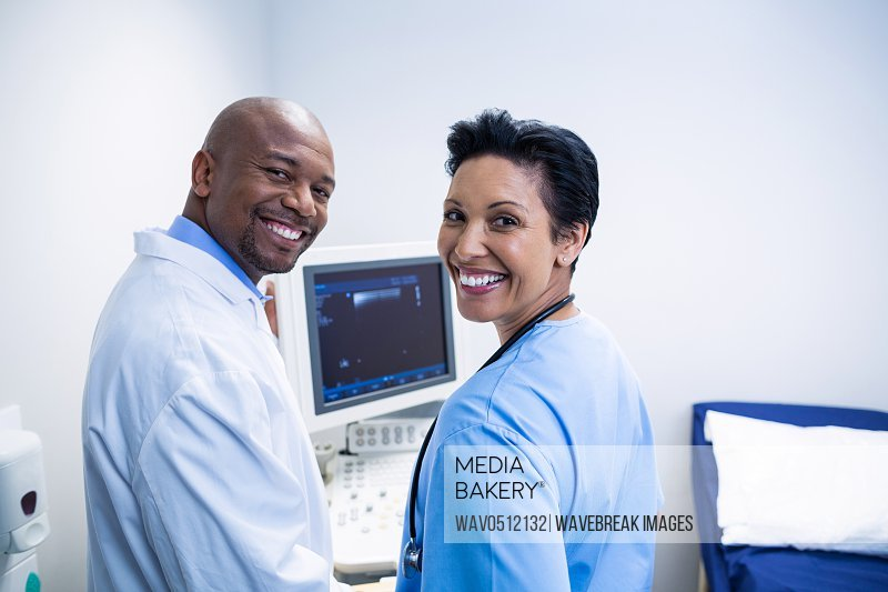Portrait of doctor and nurse standing near patient monitoring machine in ward